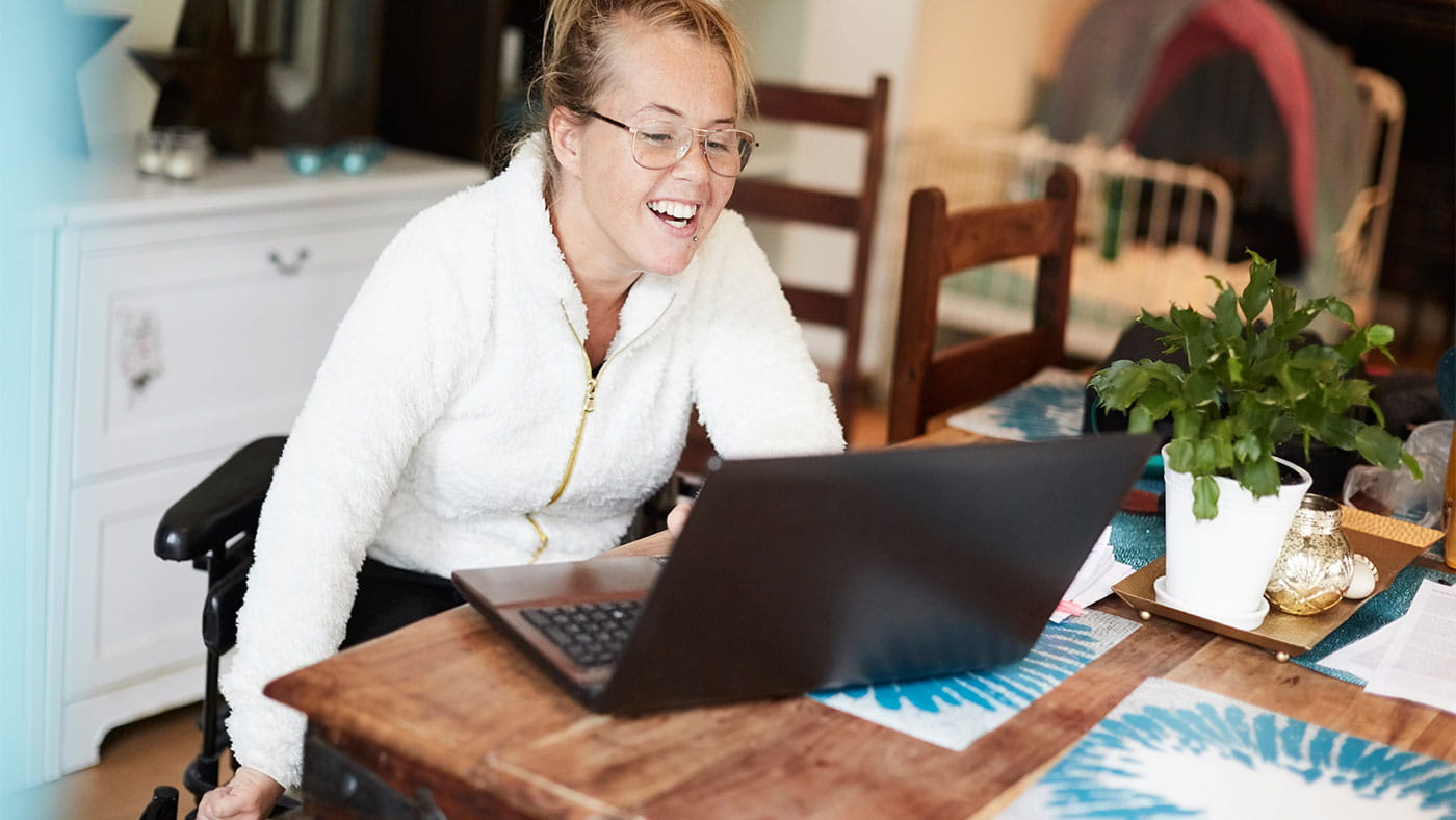 smiling woman working on a laptop in a wheelchair