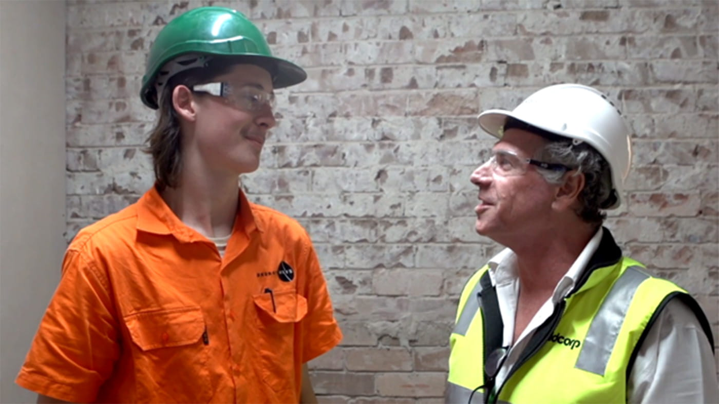 Two male Buildcorp employees looking at eachother