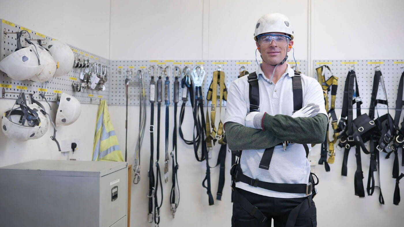 Man standing with arms crossed wearing a helmet, safety glasses, a harness in a room full of ropes and helmets