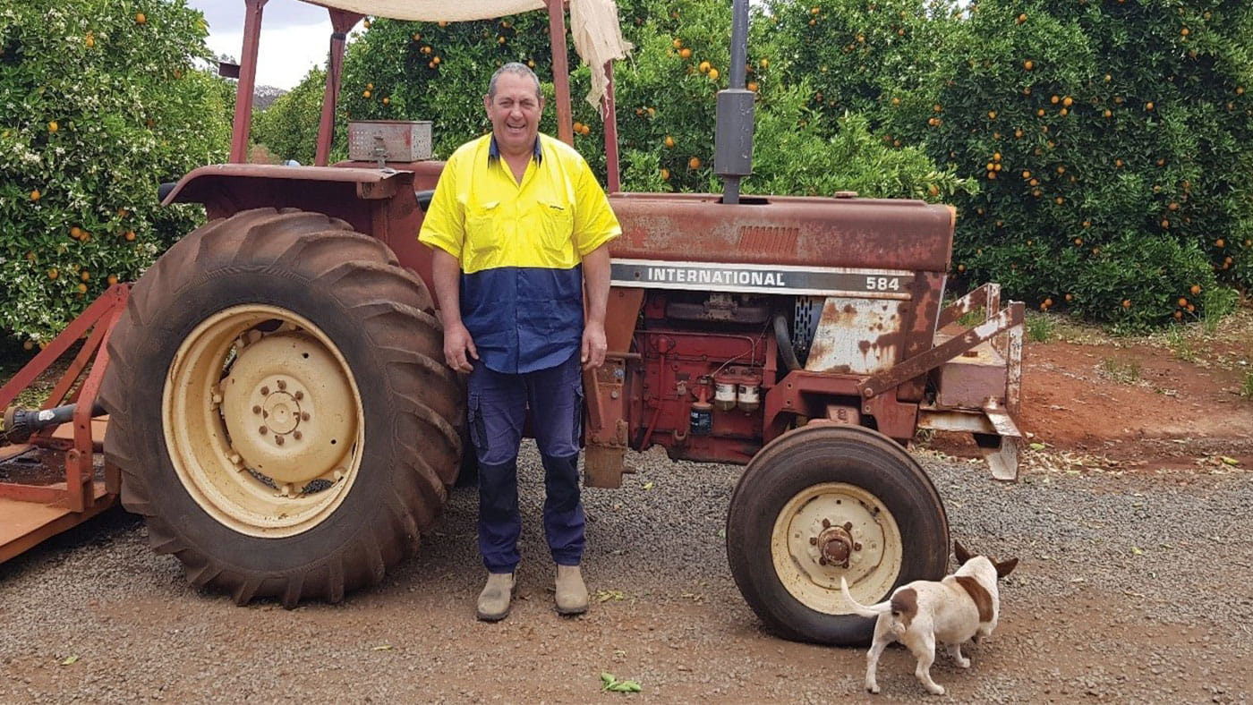 John Aloisi in front of a truck with a dog in an orchard.