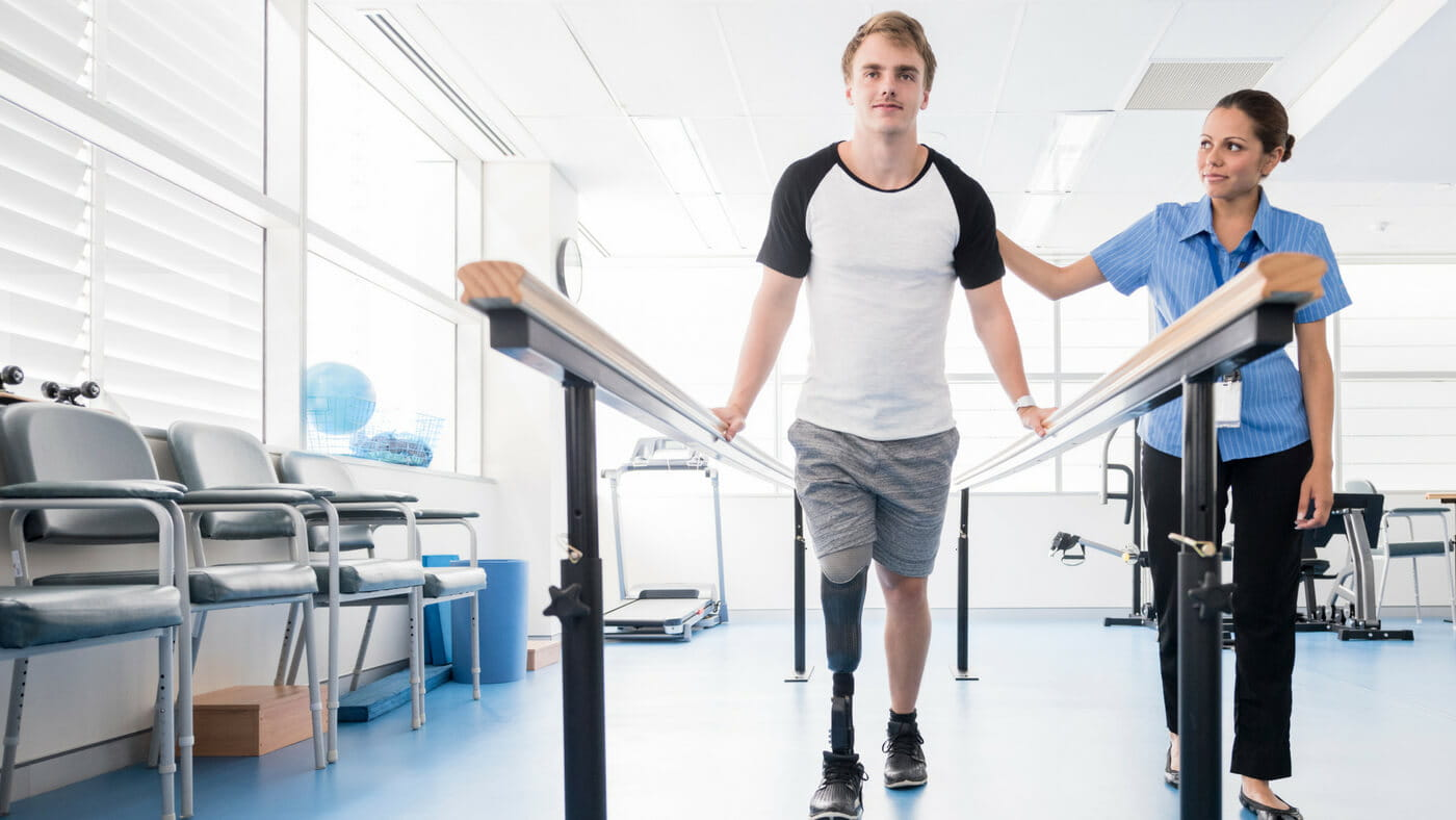 Man with prosthetic leg exercising with  a nurse attending