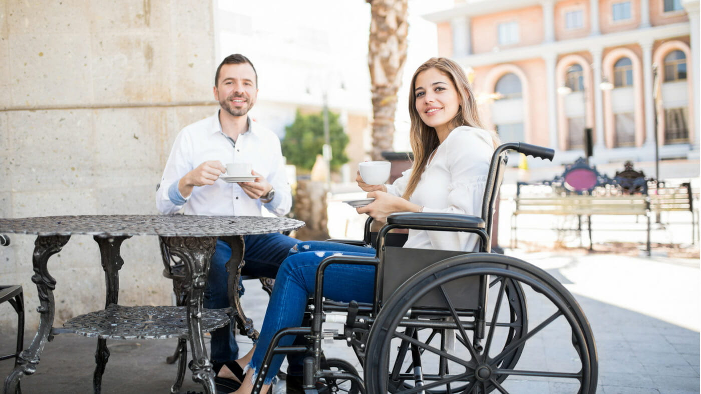 Woman in a wheelchair having coffee with a friend