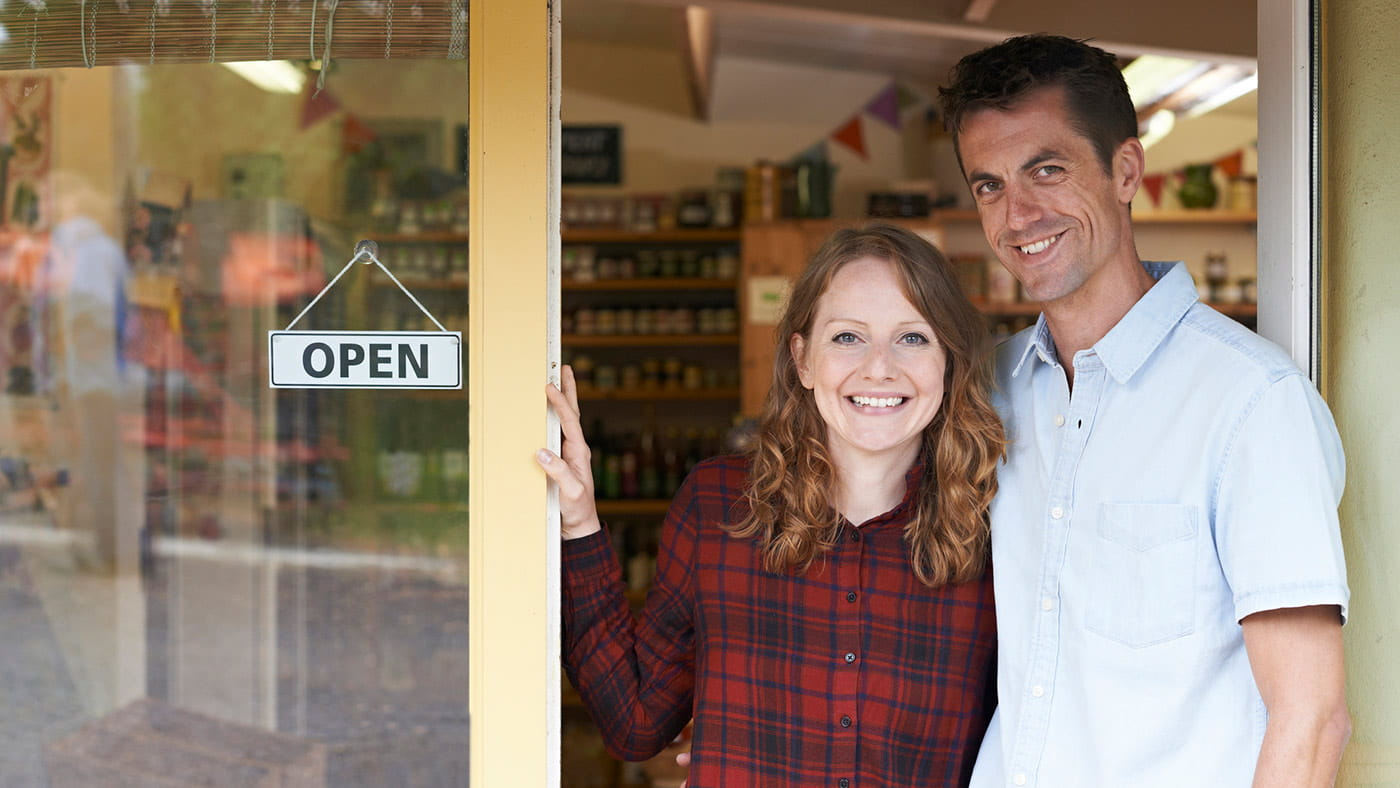 Couple standing at the entrance to their store next to an open for business sign
