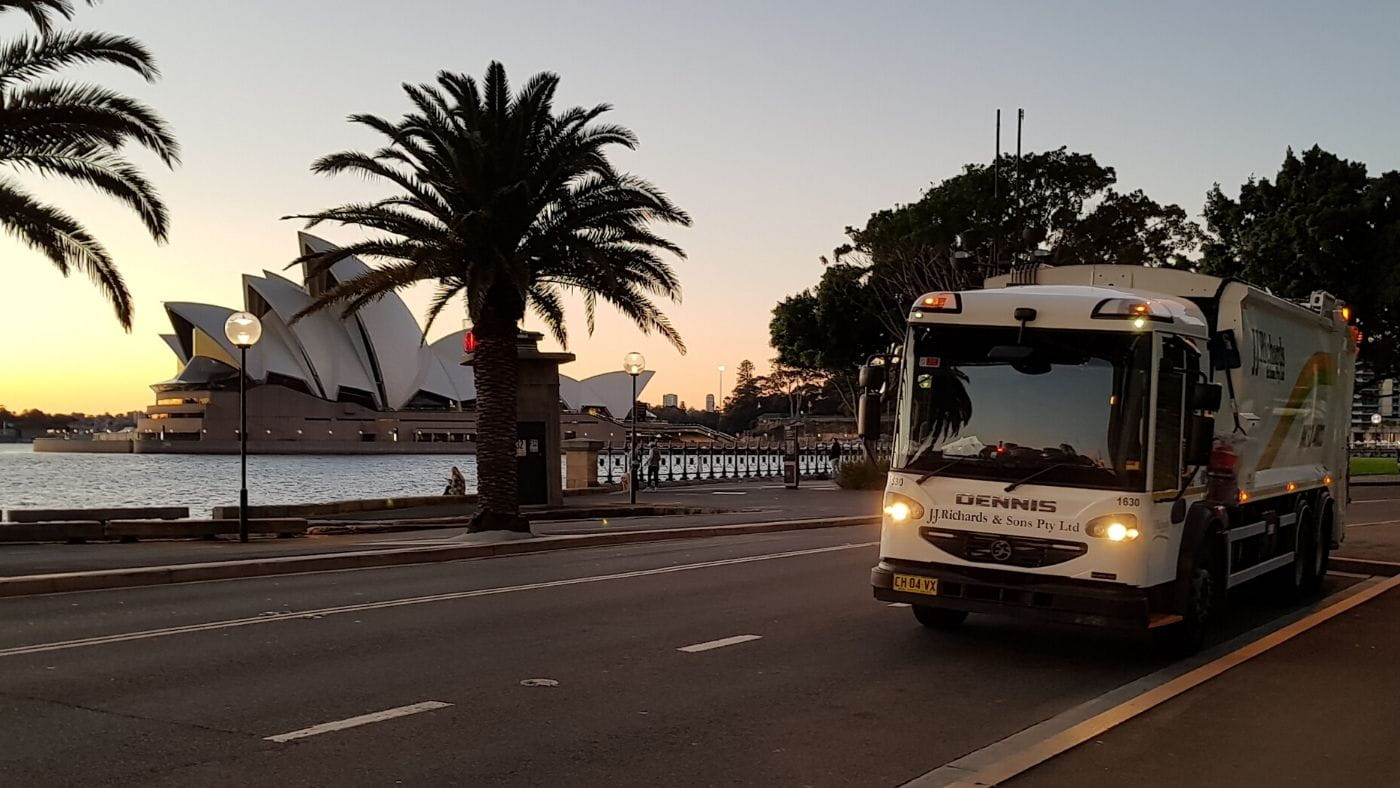JJ Richards truck driving in twilight along Sydney Harbour with Opera House in view