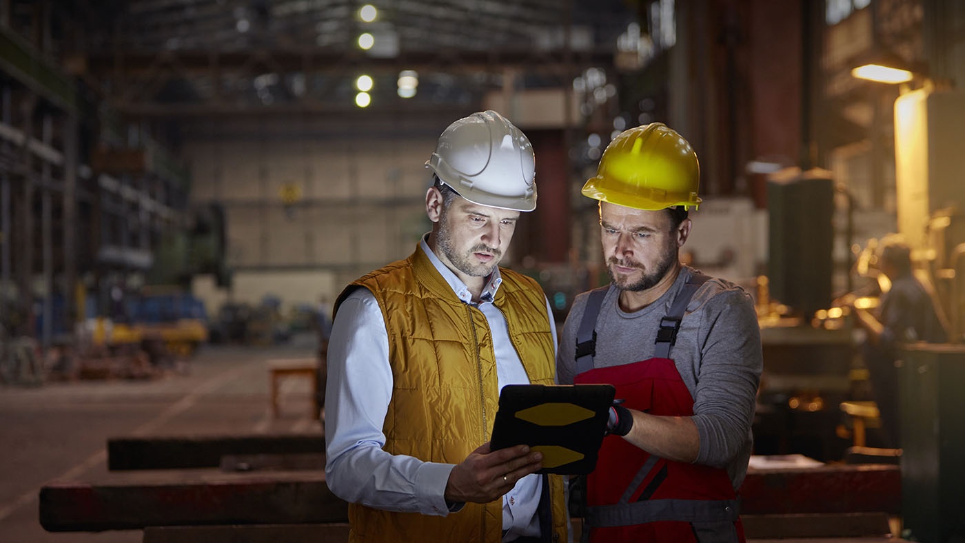 Two men in safety gear look at ipad in factory setting.