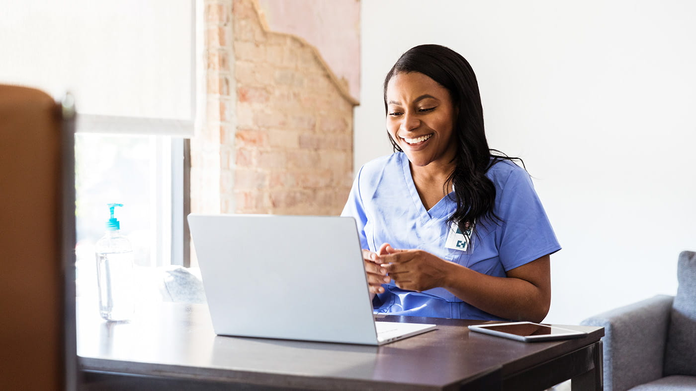A female clinician smiles while using a laptop.