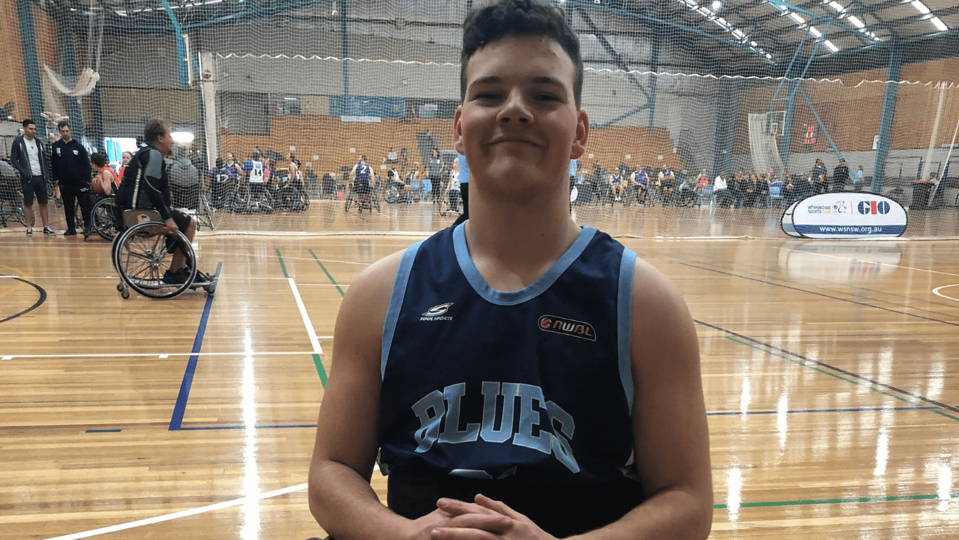 Jarrod Emeny poses in his NSW basketball jersey on court