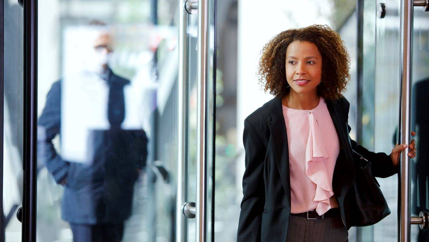 A businesswoman enters an office building