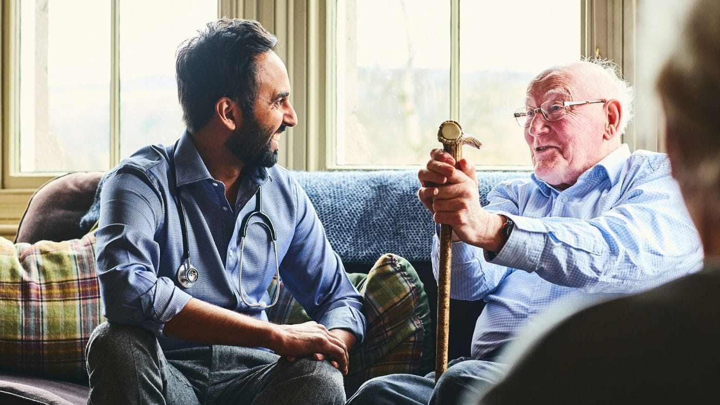 Doctor consulting with elderly man in his home