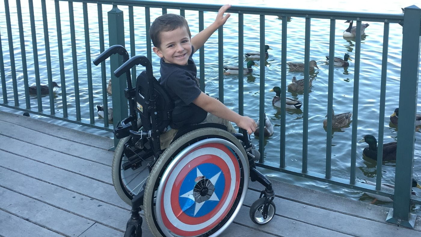 Young boy, Evander, sitting in his wheelchair by a pond feeding ducks