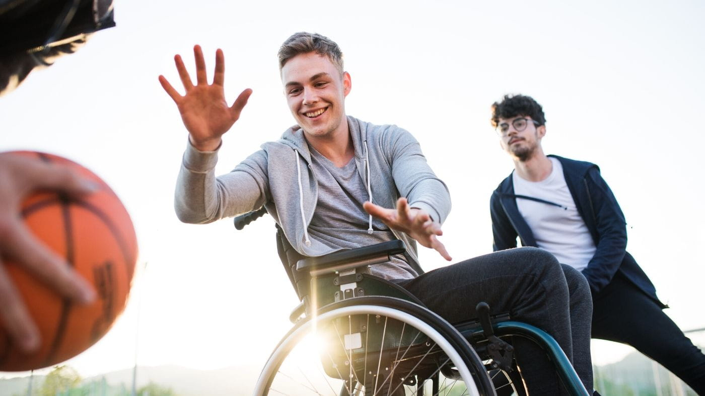 Young guy playing basketball in a wheelchair outdoors